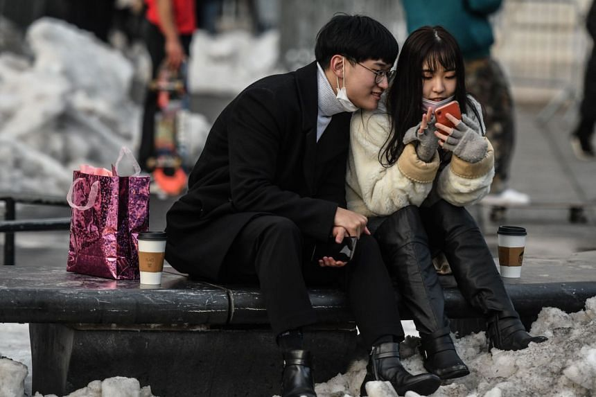 A couple looks at a mobile phone in Washington Square Park in New York, on Feb 14, 2021.