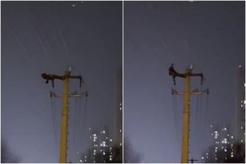 A video shows the man suspended about 10 metres in the air as he did a stomach crunch off the top of the pylon.