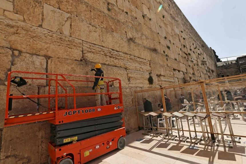 A worker using a syringe to fill fissures in boulders of the Western Wall in Jerusalem's Old City, on Feb 23, 2021.