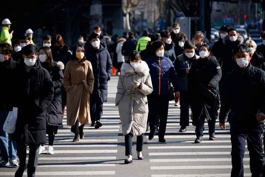 Commuters cross a zebra crossing in Seoul, South Korea, Feb 3, 2021.