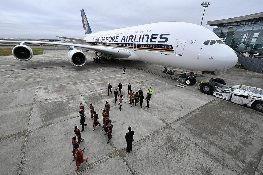 "Singapore Airlines pilots and cabin crew with the A-380 superjumbo at a delivery ceremony at the Airbus Delivery Centre in Toulouse, France, on Dec 13, 2017. The airline said it plans ""to have all 12 remaining A-380s in our fleet fitted with the late"