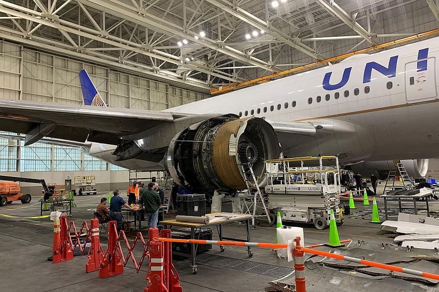 United Airlines (UA) Flight 328, a Boeing 777-200, with its damaged engine in a hangar at Denver International Airport on Monday. Part of the plane's engine caught fire and broke off during a flight at the weekend, prompting UA and other airlines to