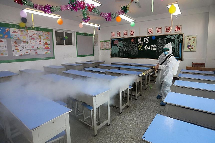 A worker spraying disinfectant in a primary school in Huaibei, Anhui province, on Feb 19 ahead of the start of a new term. The Covid-19 pandemic and the disrupted academic schedules are making millions of Chinese parents shell out money to ensure the