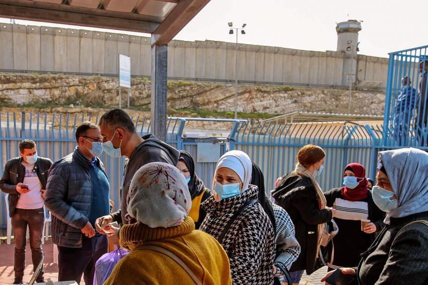 Palestinians wait to receive doses of the the Pfizer-BioNTech Covid-19 vaccine at Qalandia checkpoint on the crossing between the West Bank city of Ramallah and Israeli-annexed east Jerusalem, on Feb 23, 2021.