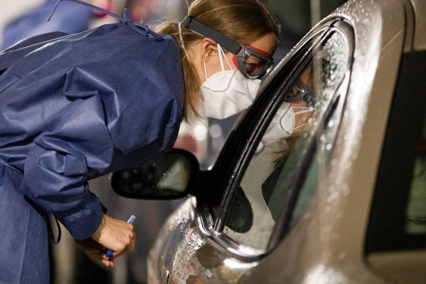 A nurse checks on a person who received a coronavirus vaccine shot at a drive-through vaccination site in Detroit, Michigan.