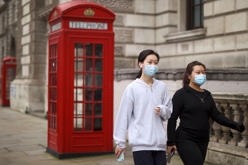 Women wearing face masks to protect against coronavirus are seen on a street in London.
