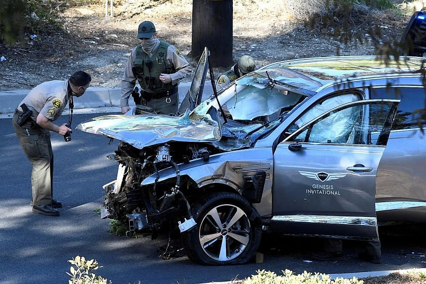 Above: Los Angeles County sheriff's deputies inspect the SUV of golfer Tiger Woods, who was involved in a single-vehicle accident near Los Angeles on Tuesday. Left: Woods' damaged car after rolling down the hillside.