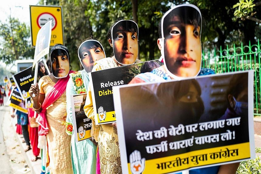 Demonstrators wearing masks with the image of climate activist Disha Ravi in New Delhi on Monday to protest against her arrest under India's sedition law earlier this month. She was released on bail on Tuesday.