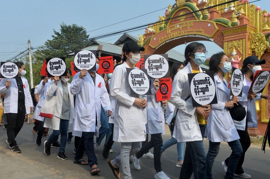 Medical students march with signs during a demonstration against the military coup in Naypyidaw, on Feb 19, 2021.