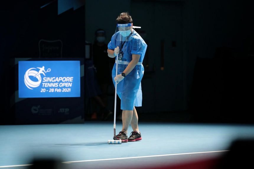 A worker prepares the court before a match at the Singapore Tennis Open at the OCBC Arena on Feb 23, 2021.
