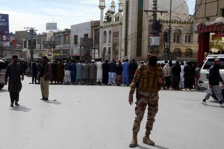 A paramilitary soldier stands guard as people offering Friday congregational prayers in Quetta, Pakistan, on Feb 12, 2021.