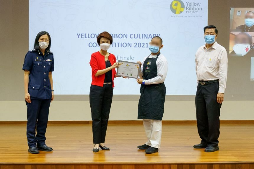 Minister of State for Trade and Industry Low Yen Ling presenting Adam (not his real name) with his award at the annual Yellow Ribbon competition on Feb 25, 2021.