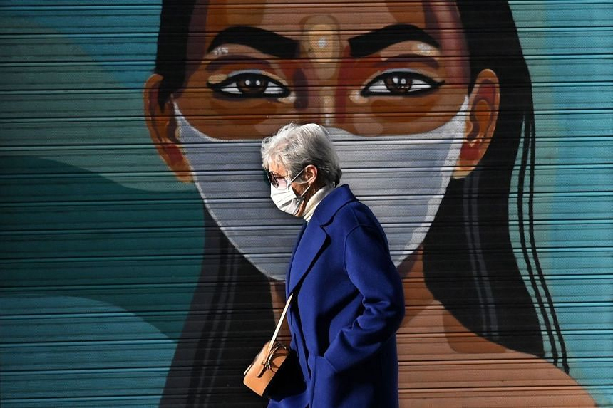 A woman walks past a mural of a young woman wearing a face mask in Madrid on Feb 24, 2021.