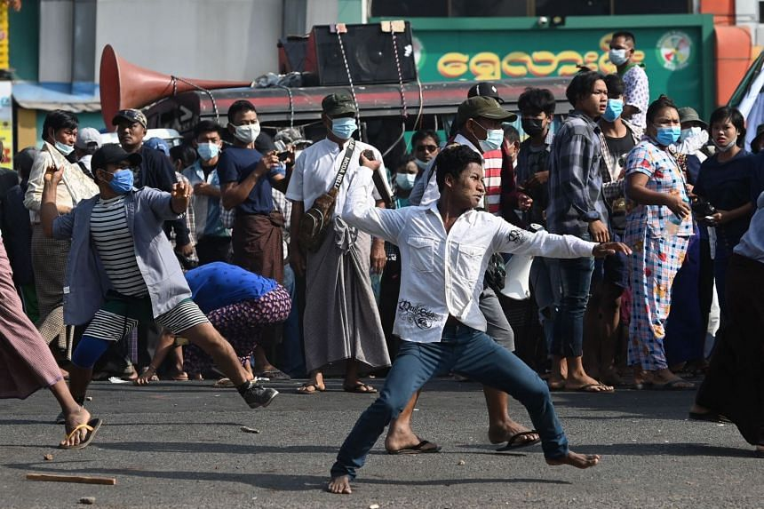 Pro-military supporters throw projectiles at residents in Yangon on Feb 25, 2021.