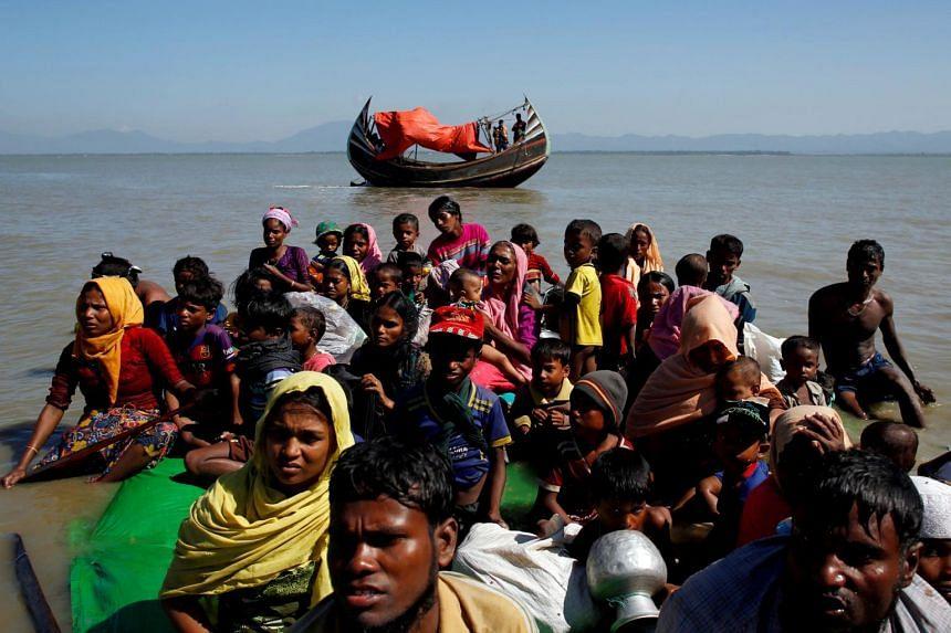 Rohingya refugees sit on a makeshift boat at Shah Porir Dwip near Cox's Bazar, Bangladesh, on Nov 9, 2017.