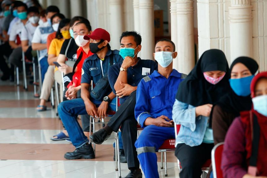People queue before receiving a vaccine for Covid-19 in Jakarta, on Feb 17, 2021.