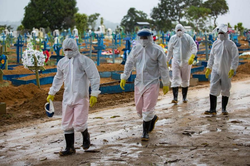 Workers wearing protective suits walk past the graves of Covid-19 victims at the Nossa Senhora Aparecida cemetery, in Manaus, Brazil, on Feb 25, 2021.