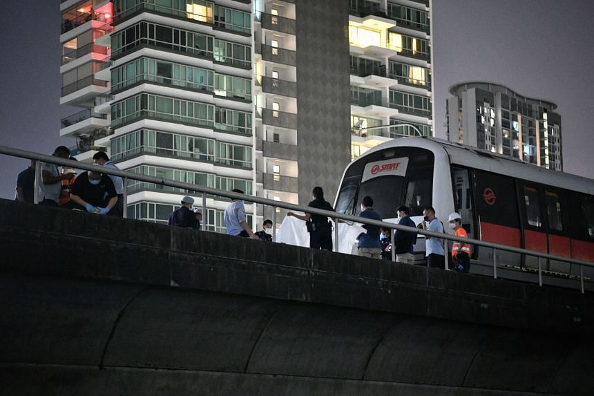 Singapore Police Force and Singapore Civil Defence Force personnel with the stationary MRT train on the east-bound track near Kallang station yesterday. SMRT said the incident took place at about 9.30pm.