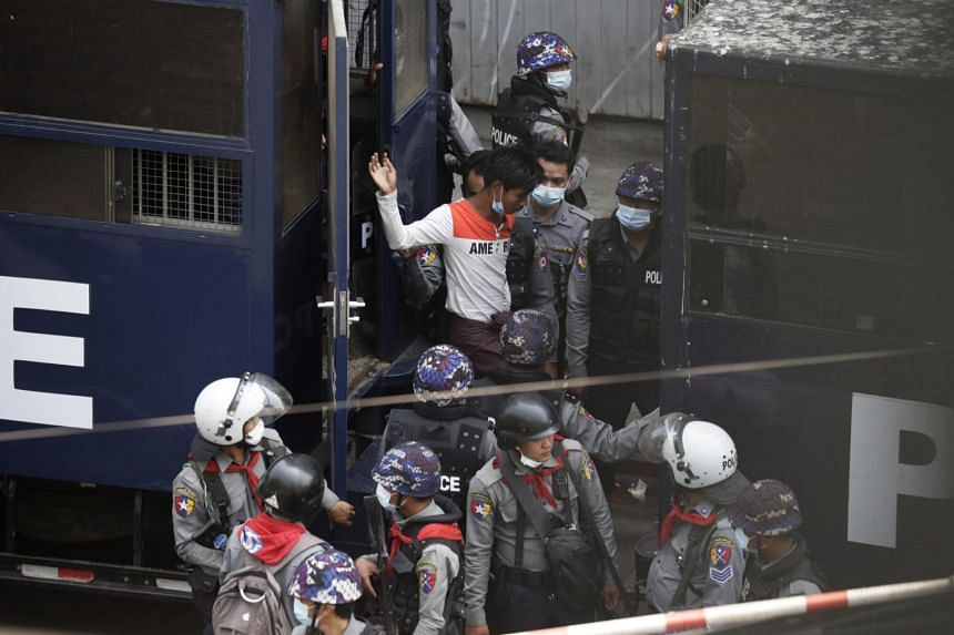 Police transfer people arrested from a vehicle to another during a protest against the military coup in Yangon on Feb 27, 2021.