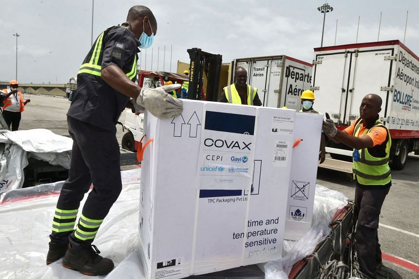 Workers unload a shipment of AstraZeneca Covid-19 vaccines bearing Covax stickers from a plane at Felix Houphouet Boigny airport of Abidjan on Feb 26, 2021.
