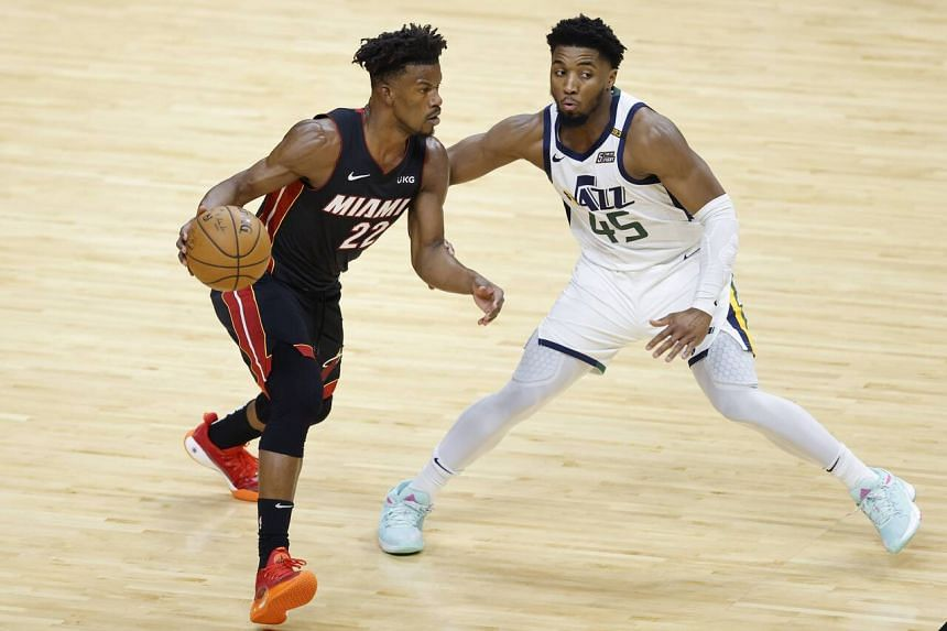 Jimmy Butler #22 of the Miami Heat drives to the basket against Donovan Mitchell #45 of the Utah Jazz.