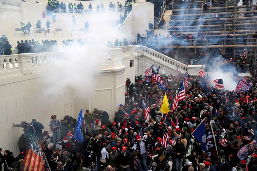 Police fire tear gas into a crowd of pro-Trump protesters during clashes at the US Capitol Building in Washington, on Jan 6, 2021.