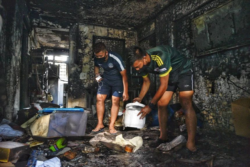 Brothers Muhammad Huzaimi Zuraimi (left) and Muhammad Haiqal Zuraimi going through their family's belongings, after a fire broke out in their flat on Feb 28, 2021.