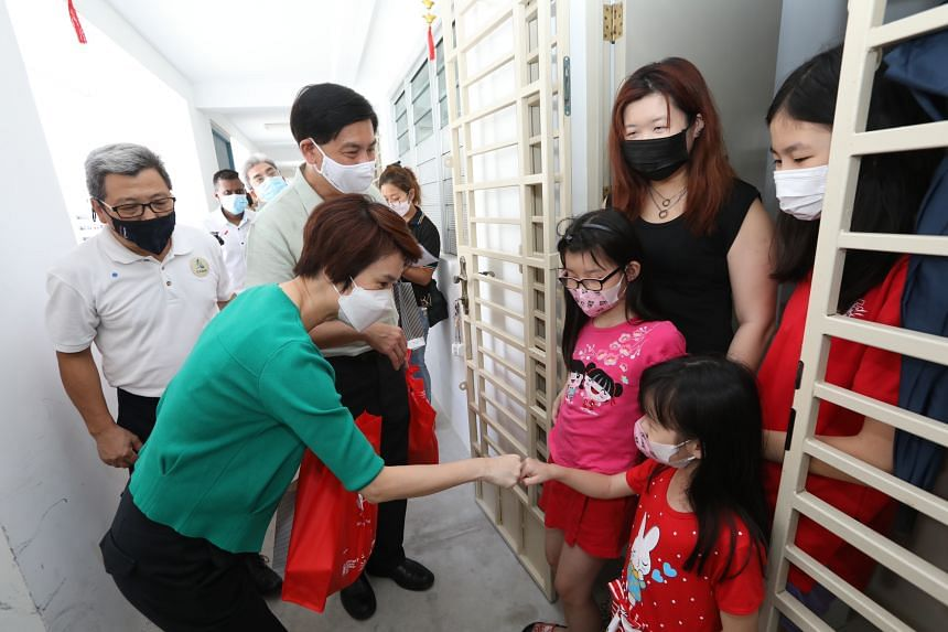 Ms Lim Siew Ching, 31, and her three daughters aged 7, 9 and 13, receiving a bundle of donated items at her flat in Jurong West, from South West District Mayor Low Yen Ling (left) in Singapore, on Feb 28, 2021.