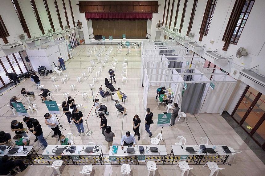 Volunteers waiting to get the Covid-19 vaccine as part of a trial run at a vaccination centre in Tanjong Pagar Community Club on Jan 26. Singapore's vaccine roll-out is expected to pick up speed. By the middle of this month, over 30 vaccination centr
