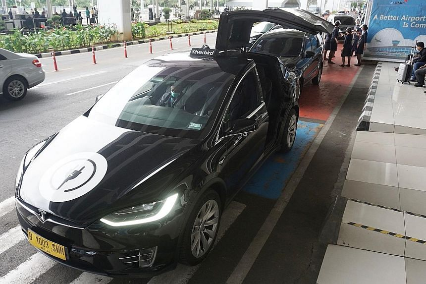 A Tesla Model X airport taxi at Jakarta's Soekarno-Hatta International Airport. Innovation and digital reform must go beyond individual businesses to include an all-of-industry response, says the writer.