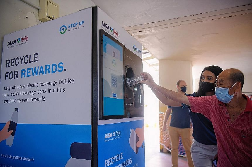 Alba W&H Smart City assistant sustainability manager Sandra Sajan helping a Jurong resident use the new reverse vending machine at Yuhua Food Centre yesterday. The food centre is one of five locations where the machines are being installed. All five