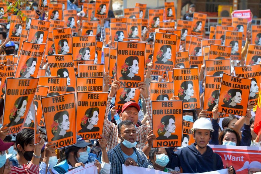 Protesters hold posters with the image of Aung San Suu Kyi during a demonstration against the military coup in Naypyitaw, on Feb 28, 2021.