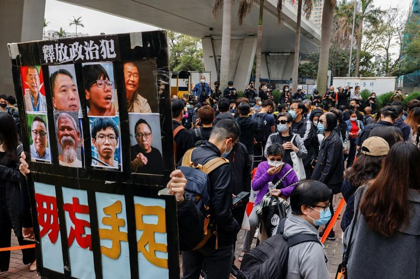 A supporter holds a sign with photos of pro-democracy activists outside West Kowloon Magistrates' Courts in Hong Kong, on March 1, 2021.