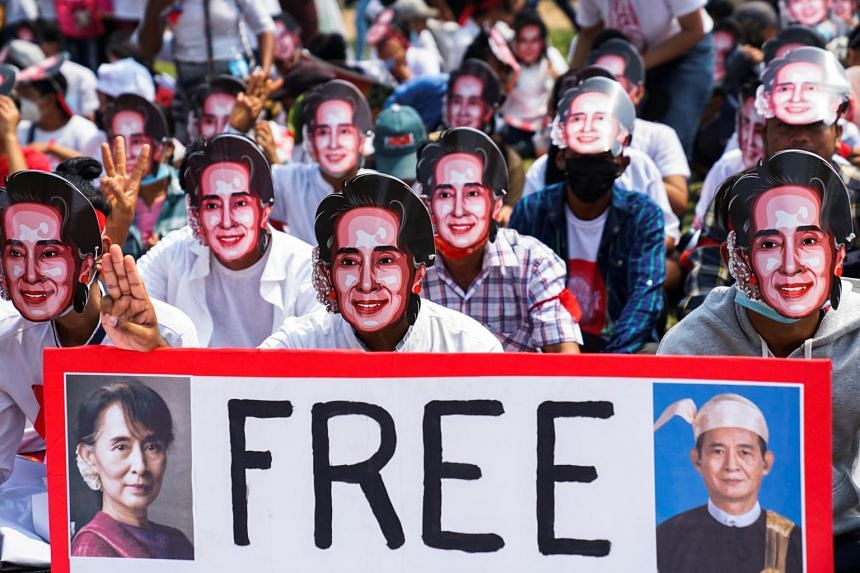 Protesters wearing masks flash three-finger salutes as they take part in a protest against the military coup in Yangon, on Feb 28, 2021.