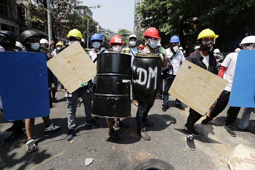 Demonstrators hold shields as they face riot police during a protest against the military coup in Yangon, on Feb 28, 2021.
