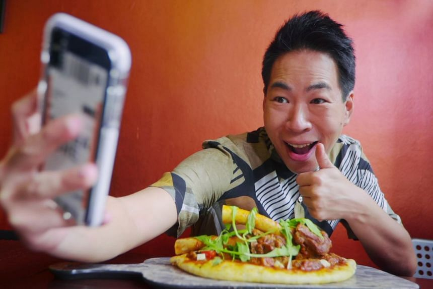 "Chua Enlai having a moment with his toolang ""pizza"", also known as the Battleship, at Tash Tish Tosh. Watch the video embedded in this story! PHOTO: SPH"