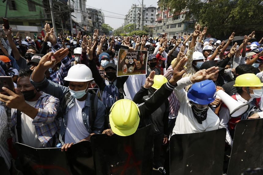 Demonstrators flash the three-finger salute during a protest against the military coup in Yangon, on Feb 28, 2021.
