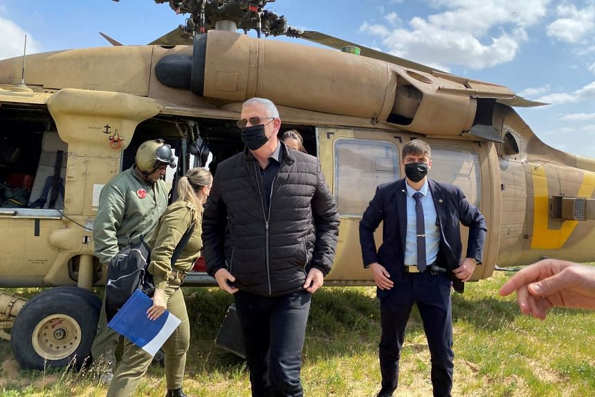 Israeli Defence Minister Benny Gantz (centre) adjusts his jacket after stepping off a helicopter during a tour of the Gaza border area on March 2, 2021.
