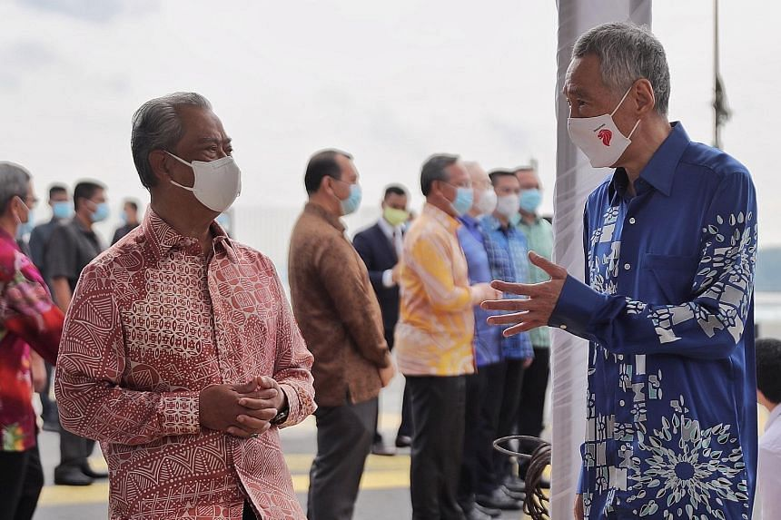 Prime Minister Lee Hsien Loong and Malaysian Prime Minister Muhyiddin Yassin at a ceremony at the Causeway last July to mark the official resumption of the Rapid Transit System Link project. ST PHOTO: GAVIN FOO Foreign Minister Vivian Balakrishnan wi