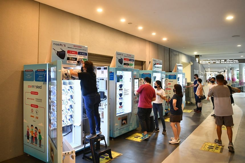 A women stocking up the mask vending machines at Our Tampines Hub on March 2, 2021.