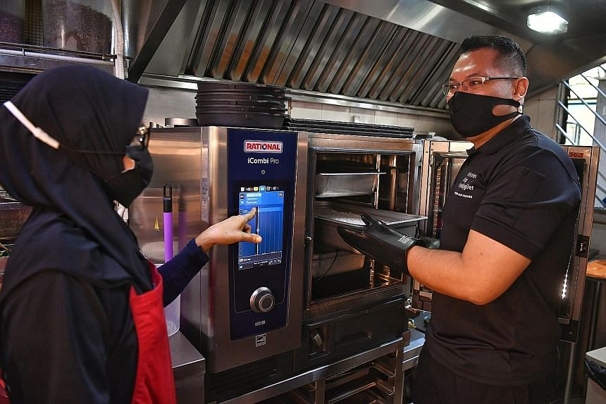 Mr Abdul Hadi Kamarolzaman, director of Istimewa Nasi Padang, using a combi oven at one of the company's two outlets yesterday. The oven enables staff to cook multiple dishes at the same time, without affecting the taste and aroma. ST PHOTO: CHONG JU