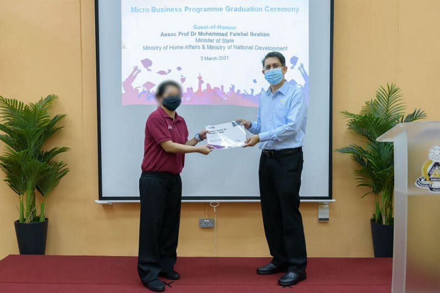 Minister of State Muhammad Faishal Ibrahim presents a certificate to one of the 18 inmates who graduated from AMP's Micro Business Programme, on March 3, 2021.