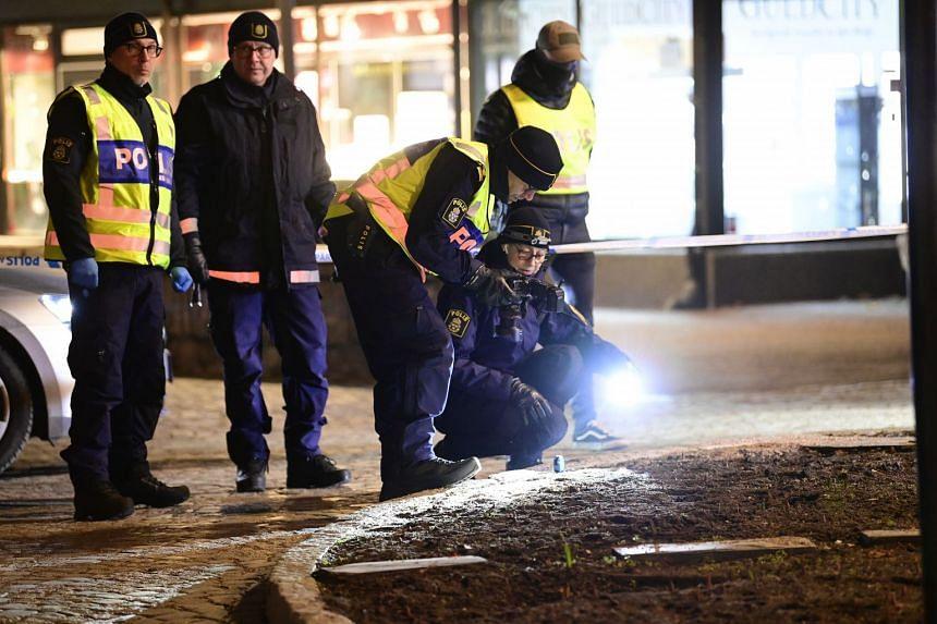Police technicians investigate the scene of the attack in central Vetlanda.