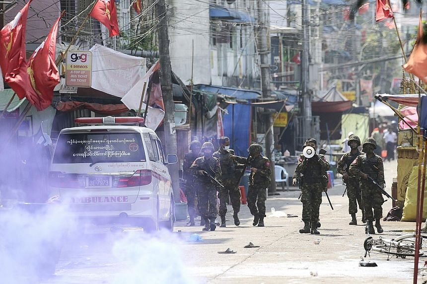 DANGER: Protesters facing off against the police during a demonstration in Mandalay yesterday against Myanmar's military coup. PHOTO: AGENCE FRANCE-PRESSE TAKING COVER: Protesters in Yangon hiding behind makeshift shields (left) during a demonstratio