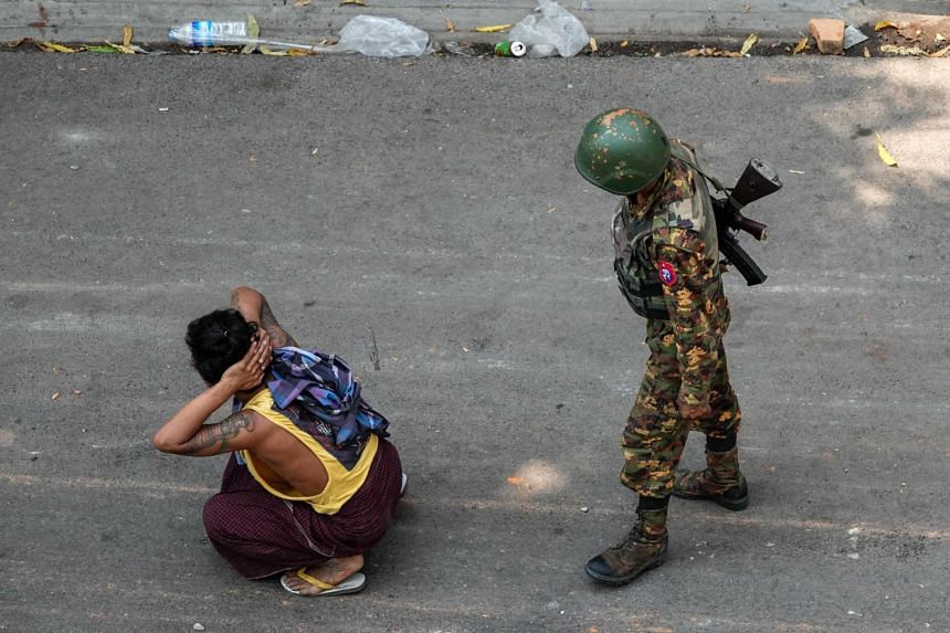A soldier stands next to a detained man during a demonstration against the military coup in Mandalay, Myanmar, on March 3, 2021.
