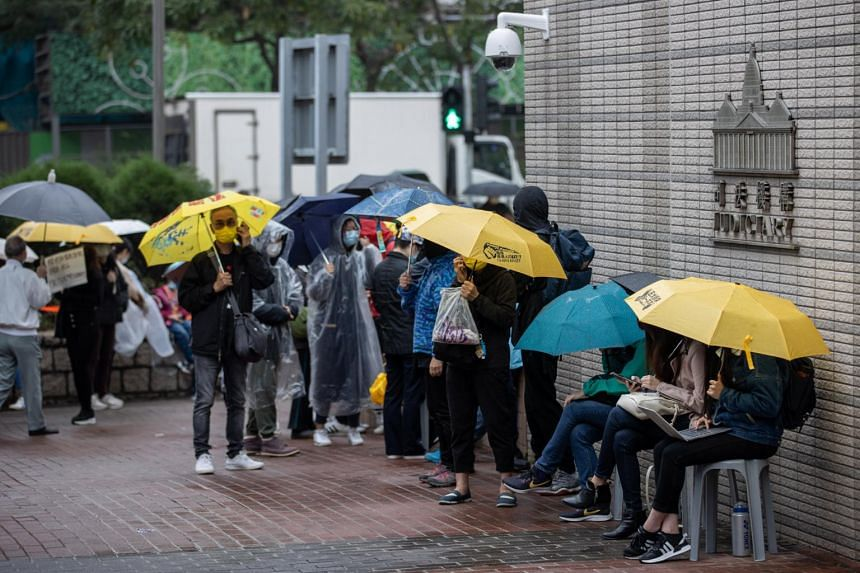 Supporters of democracy activists line up outside the West Kowloon court building in Hong Kong on March 4, 2021.
