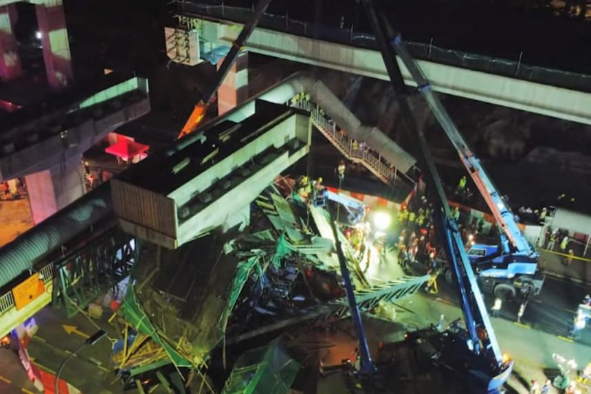 A trailer lorry carrying an excavator was believed to have hit the scaffolding of the pedestrian bridge near a major highway.