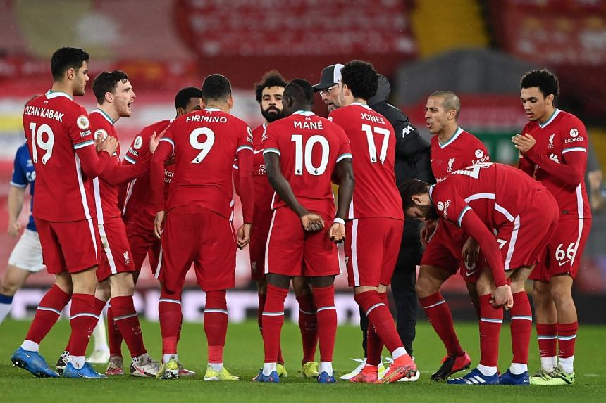 Klopp gathers his players on the pitch for a team talk ahead of the second half of a match between Liverpool and Everton.