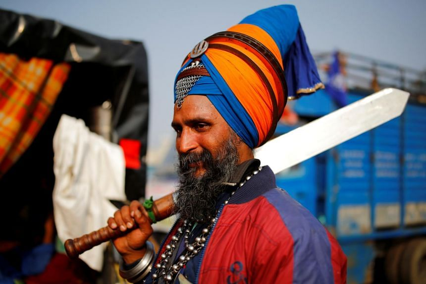 A Sikh warrior holds a sword as he stands next to police barricades at the site of a protest  at Singhu border on Dec 7, 2020.
