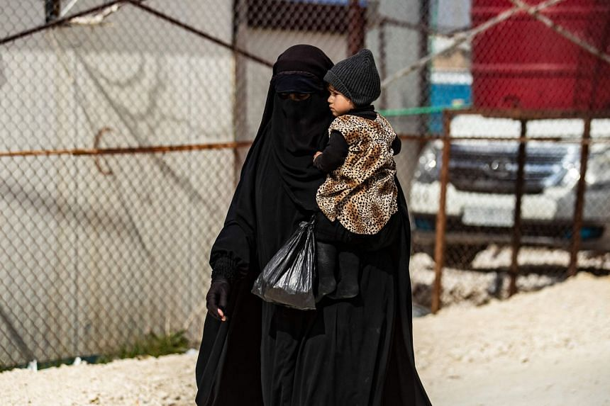 A woman carries a child as she walks at the Kurdish-run Al-Hol camp which holds suspected relatives of ISIS group fighters, in Syria, on March 3, 2021.